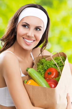 only: Portrait of cheerful smiling young beautiful brunette woman in fitness wear holding grocery shopping bag with healthy vegetarian raw food, outdoor. Healthy lifestyle, beauty and dieting concept. Stock Photo
