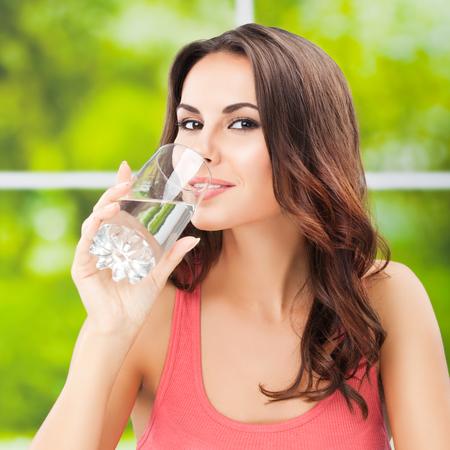vaso con agua: Retrato de mujer joven feliz con un vaso de agua Foto de archivo