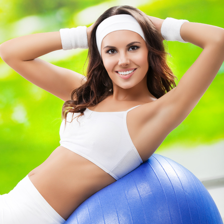 fitball: Portrait of beautiful smiling woman exercising with fitball, outdoor