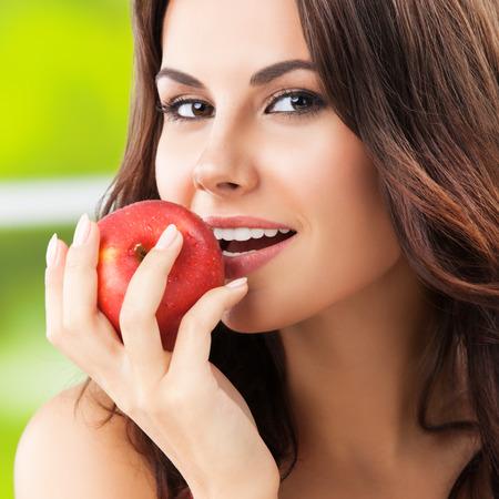 comiendo frutas: Mujer sonriente feliz joven con la manzana roja