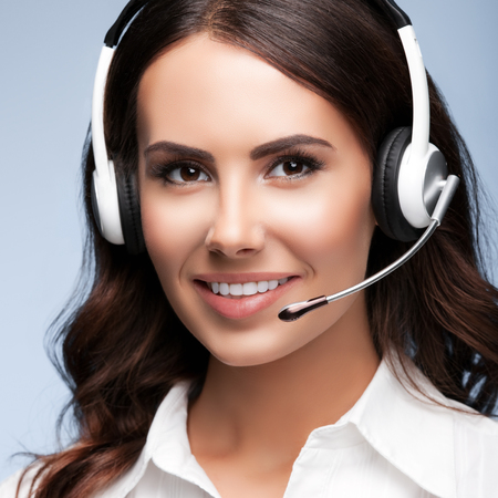 hands free phones: Portrait of smiling cheerful customer support female phone worker, against grey background. Consulting and assistance service call center.