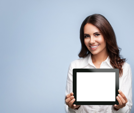 Smiling beautiful young brunette businesswoman showing blank no-name tablet pc monitor, over grey background, with copyspace area for slogan or text message