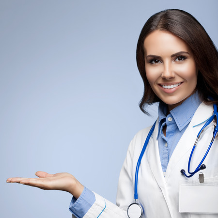 medicaid: Portrait of happy smiling young doctor showing something or blank copyspace for slogan or text message, on grey background Stock Photo