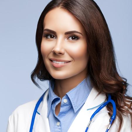 medicaid: Portrait of happy smiling female doctor, on grey background Stock Photo