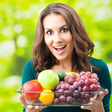 summer fruit: Young happy smiling woman with plate of fruits, outdoors, with copyspace for text or slogan. Stock Photo