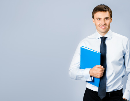 folders: Portrait of happy smiling young business man with blue folder, with copyspace, over grey background Stock Photo