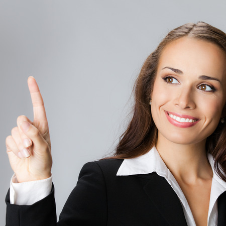 copyspase: Happy smiling young business woman showing blank area for sign or copyspase, over grey background