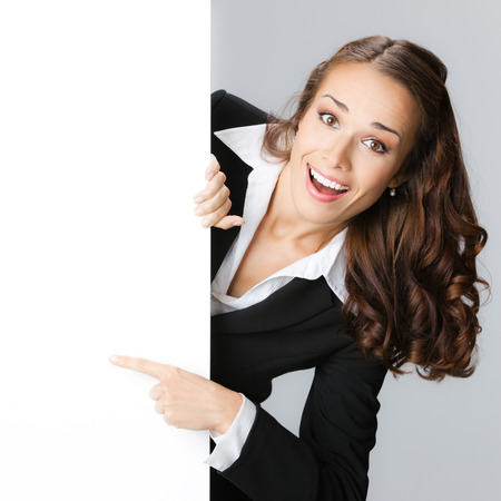 signboard: Happy smiling young business woman showing blank signboard, over grey background