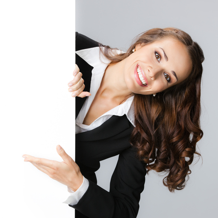 executive women: Happy smiling young business woman showing blank signboard, over grey background