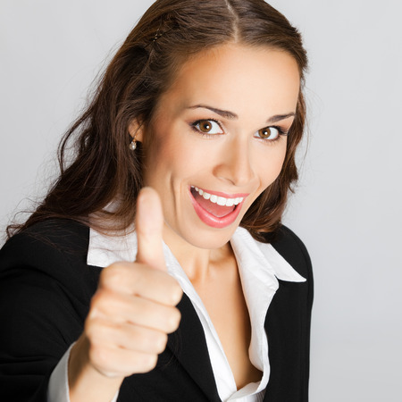 good work: Happy smiling business woman showing thumbs up gesture, over grey background
