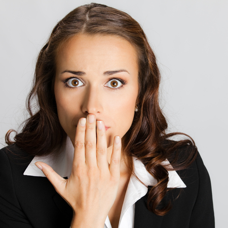excited people: Portrait of surprised excited young business woman covering with hands her mouth, over grey background Stock Photo