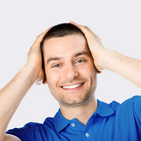 mid thirties: Expressive happy surprised man, against grey background Stock Photo