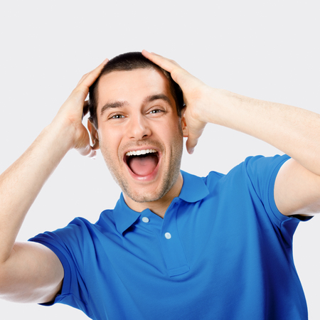 expressive: Expressive happy surprised man, against grey background Stock Photo