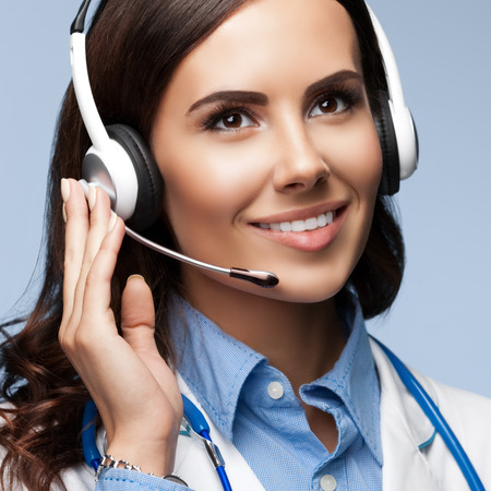 call: Portrait of happy smiling young doctor in headset, on grey background