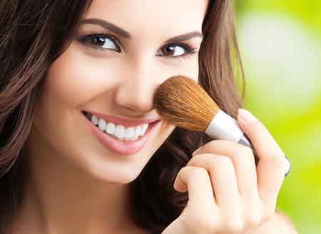 bella donna sorridente con make up pennello, esterno Archivio Fotografico