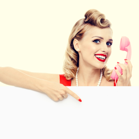 blank center: woman with phone, in pin-up style dress, showing blank signboard with copyspace area. Caucasian blond model posing in retro fashion and vintage concept studio shoot.