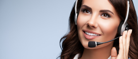 hands free phones: Portrait of cheerful support female phone operator in headset, against grey background, with copyspace area for slogan or text message. Consulting and assistance service call center.