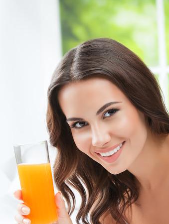 tomando jugo: Retrato del joven hermosa mujer morena beber jugo de naranja sonriendo. alimentación saludable, la belleza y el concepto de dieta.