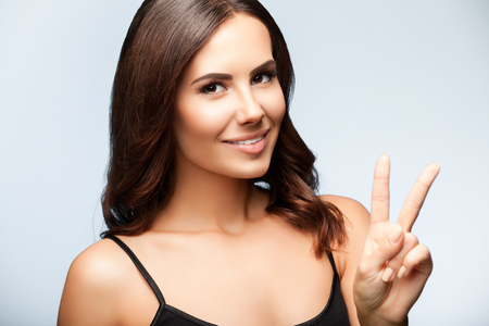 two persons only: woman in black tank top clothing, showing two fingers or victory gesture, on bright grey background Stock Photo
