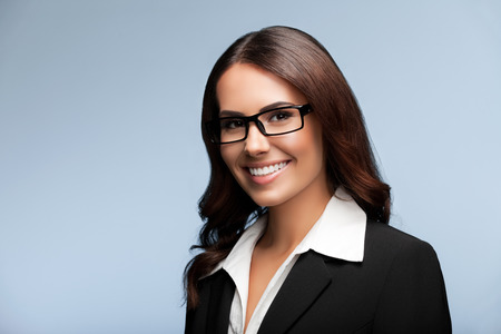 Portrait of happy smiling young brunette businesswoman in glasses, over grey background