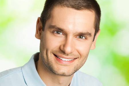 uomo felice: Ritratto di giovane uomo felice sorridente con piatto di frutta, all'aperto