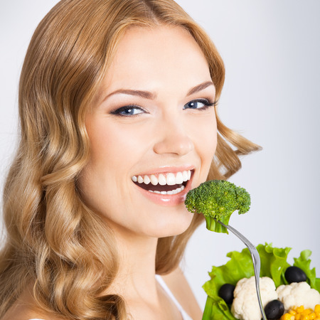 beautiful salad: Portrait of happy smiling young beautiful woman with healthy vegetarian salad, over gray background Stock Photo