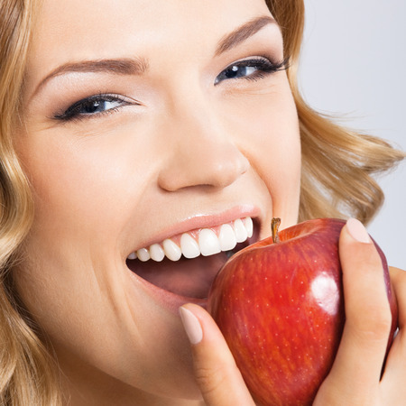 woman eat: Portrait of happy smiling young beautiful woman eating red apple, over gray background