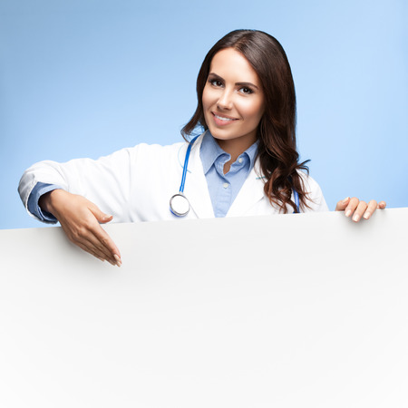 Portrait of happy smiling female doctor showing blank signboard with copyspace for slogan or text, on bright blue background