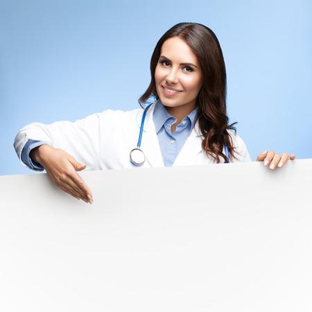 letreros: Retrato de la sonrisa feliz médico femenino que muestra la señal en blanco con copyspace de lema o texto, sobre fondo azul brillante Foto de archivo