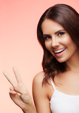 two persons only: Portrait of beautiful young woman showing two fingers or victory gesture, on light red background Stock Photo