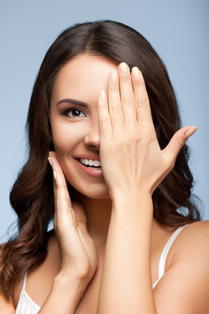 one eye: Concept photo of happy smiling young woman with one eye, closed by hand, covering part of her face, over grey background
