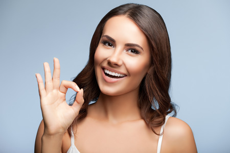 two persons only: Portrait of happy smiling young beautiful woman showing okay or zero hand gesture, over grey background Stock Photo