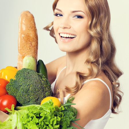 comiendo pan: Portrait of happy smiling young beautiful woman with healthy vegetarian raw food