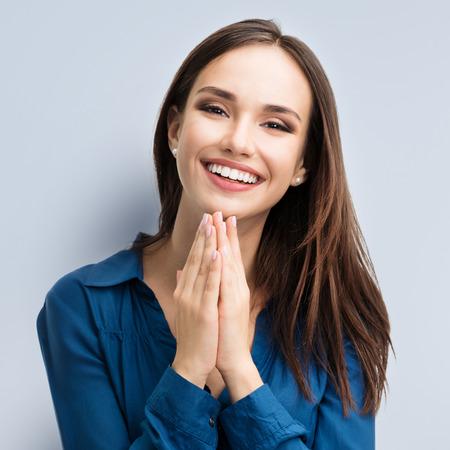カジュアル スマート青い服で幸せなジェスチャー笑顔若い女の肖像