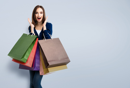 woman bag: Very happy beautiful young woman in casual clothing with shopping bags, with copyspace for slogan or text message