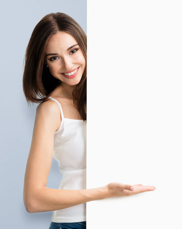 Portrait of happy smiling young woman in white tank top casual smart clothing, showing empty blank signboard with copyspace area for text or slogan