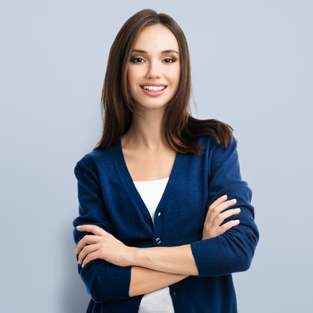 casual clothing: Portrait of young smiling woman in casual smart blue clothing with crossed arms Stock Photo