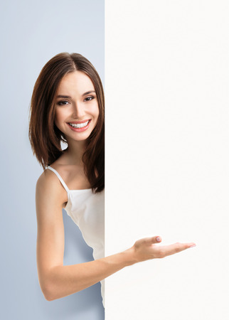 empty tank: Portrait of happy smiling young woman in white tank top casual smart clothing, showing empty blank signboard with copyspace area for text or slogan