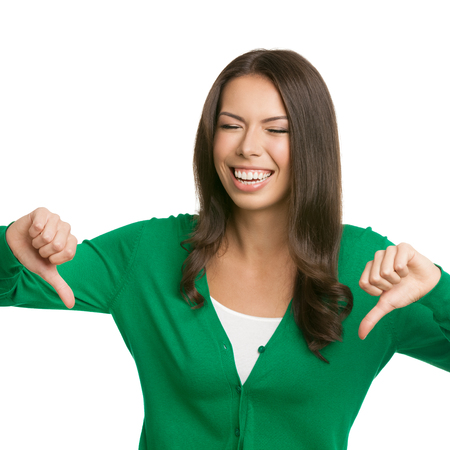 isolated on green: Portrait of happy young woman in green casual smart clothing, showing thumbs down gesture, isolated against white background