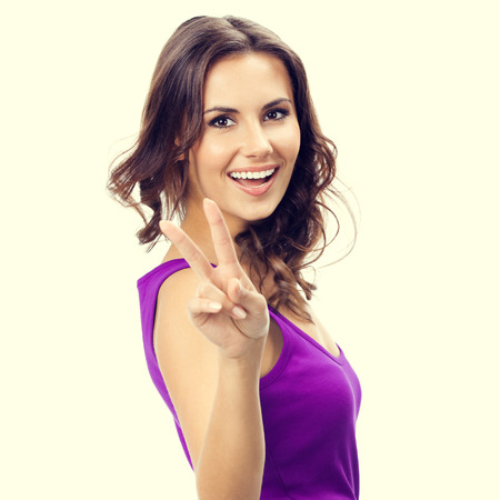two persons only: Happy beautiful young woman in casual smart lilac clothing, showing two fingers or victory gesture Stock Photo
