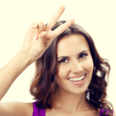 two persons only: Happy smiling young woman showing two fingers or victory gesture. Selective focus on hand.