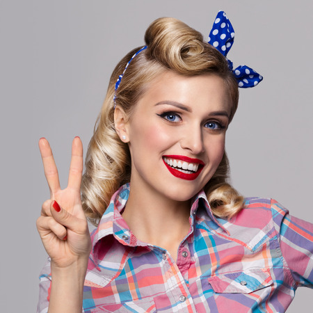 good grooming: Portrait of beautiful young happy smiling woman, showing two fingers or victory gesture, dressed in pin-up style. Caucasian blond model posing in retro fashion and vintage concept studio shoot, on grey background. Stock Photo