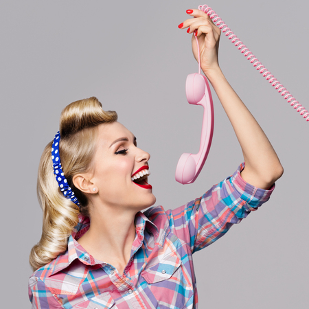good grooming: Portrait of beautiful young happy woman with phone, dressed in pin-up style. Caucasian blond model posing in retro fashion and vintage concept studio shoot, on grey background.
