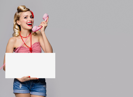 good grooming: Portrait of beautiful young happy smiling woman with phone and blank signboard, dressed in pin-up style. Caucasian blond model posing in retro fashion and vintage concept studio shoot, on grey background. Stock Photo