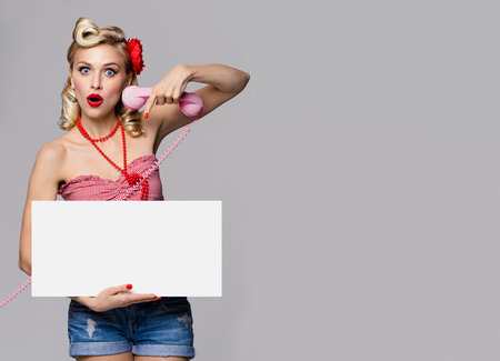 blank center: Portrait of beautiful young woman with phone and blank signboard, dressed in pin-up style. Caucasian blond model posing in retro fashion and vintage concept studio shoot, on grey background.