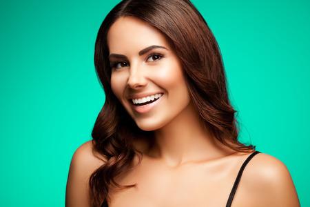 belle brune: portrait de la belle jeune femme souriante en noir débardeur vêtements, sur fond vert