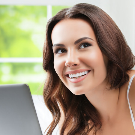 laptop home: Cheerful young woman using laptop, at home