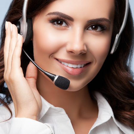 handsfree phones: Portrait of smiling support female phone operator in headset, against grey background. Consulting and assistance service call center.