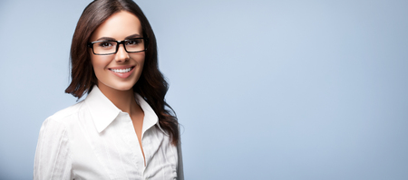business attire teacher: Portrait of happy smiling brunette businesswoman in glasses, over grey background, with blank copyspace area for slogan or text