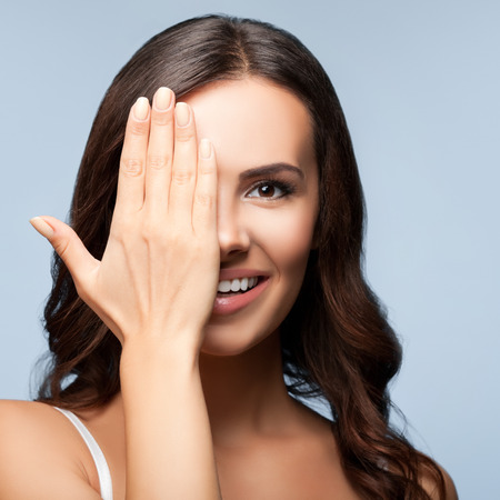 eye closed: Concept photo of happy smiling young woman with one eye, closed by hand, covering part of her face, over grey background